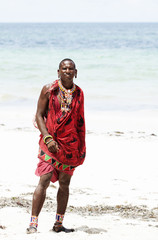 Young massai warrior man posing on bright sunny beach in Kenya