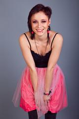 Elegant brunette girl with earrings in pink and black dress