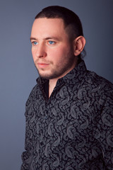 Portrait of serious business man in black shirt with patterns