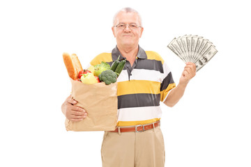 Senior holding a grocery bag and money