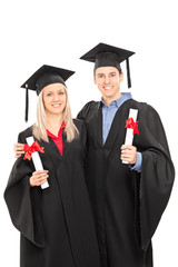 Man and woman in graduation gowns holding diplomas