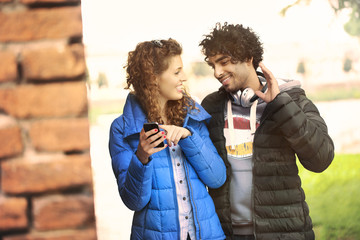 Couple looking at a mobile phone and listening music