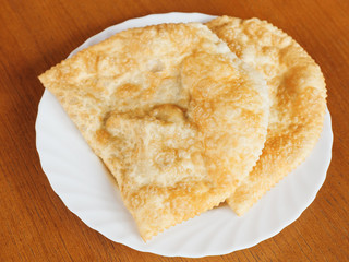top view of cheburek pie on white plate