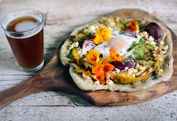Root vegetables pizza with cottage cheese, egg and flowers