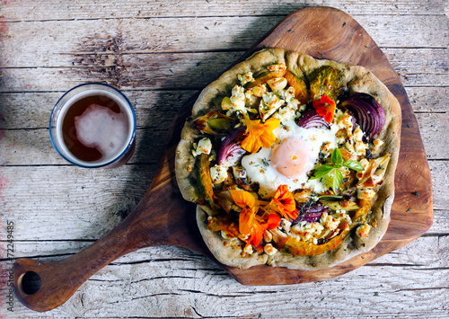 Pizza with root vegetables, cottage cheese, egg and flowers