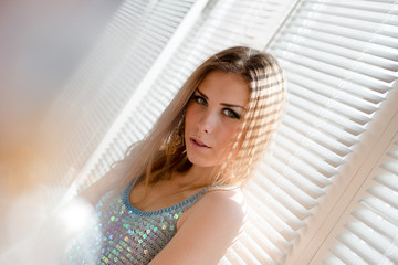 beautiful blond young woman on sun flare window blinds