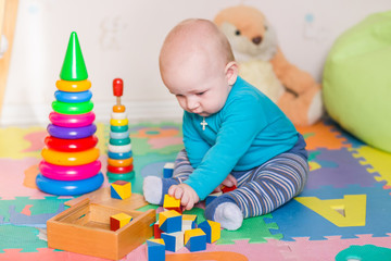 Cute little baby playing with colorful toys indoors