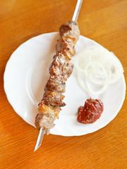 skewer of lamb shish kebab on white plate