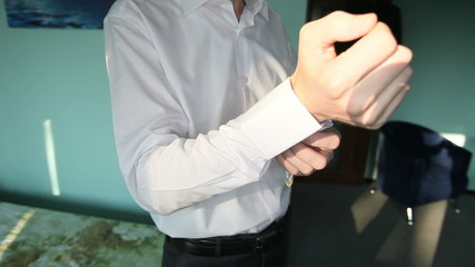 groom straightens cuffs on the sleeves of his white shirt