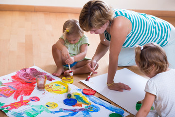 Mother and siblings painting with paint