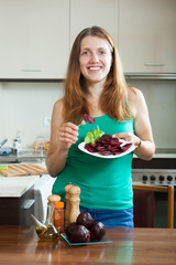 Cheerful  girl in green eating boiled beets