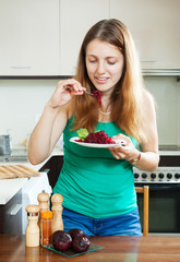 girl in green eating  beets