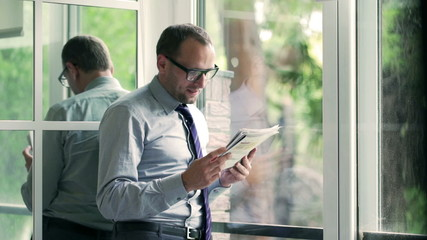 Happy businessman reading newspaper next to the window