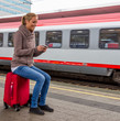 Frau wartet auf Zug und schreibt SMS