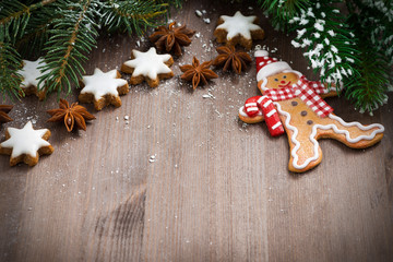 dark wooden background with fir branch, cookies and gingerbread