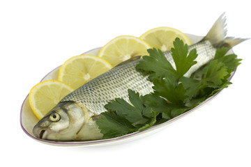 Raw fish with lemon and parsley isolated on white background