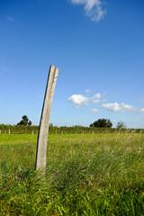 Holzpflock in bäuerlicher Landschaft