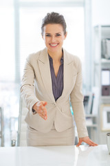 Portrait of happy business woman stretching hand for handshake