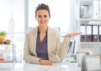 Business woman presenting something on empty palm in office