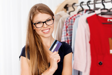 Young happy female with credit card ready for purchases.