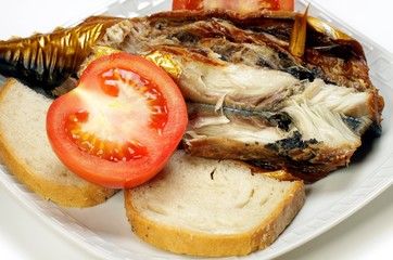 Smoked mackerel, tomatoes and bread on a white plate