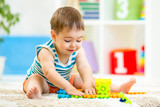 child boy playing with block toys indoor poster