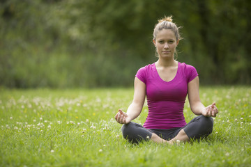 Close Pretty Woman in Yoga Pose on Grassland