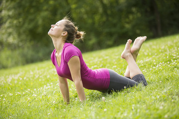 Attractive Young Woman Stretching at Grassy Ground
