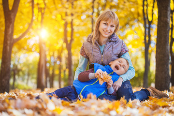 mother and her kid have fun in the autumn park