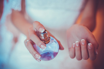 woman applying perfume on her wrist