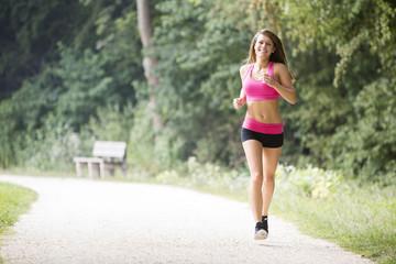 Young woman jogging through a park