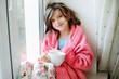 Beautiful little girl in bathrobe with cup of tea