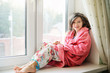 Beautiful little girl in bathrobe near window