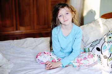 Kid girl on bed in the bedroom
