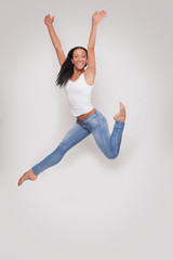 Young woman having fun jumping in studio