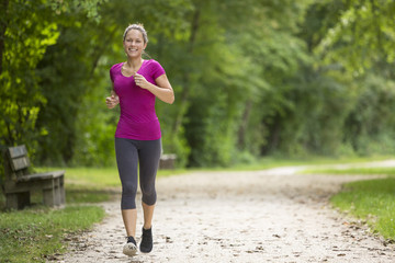 Happy relaxed woman jogging through a park