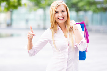 Woman with shopping bags showing thumbs up