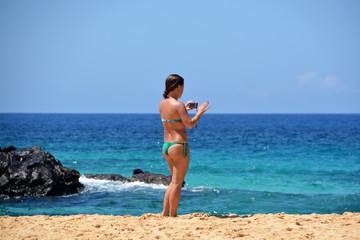 mujer fotografiando en la playa
