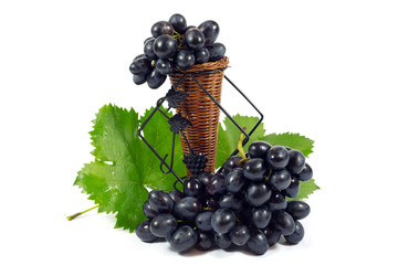 Fresh Red Grapes with Green Leaves in Wicker Basket Isolated