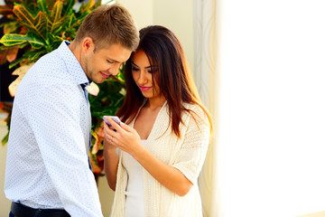 Happy couple using smartphone at home