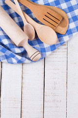 Wooden spoons, roller on towel on table.