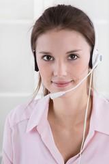 Lachende Frau mit Headset im Callcenter