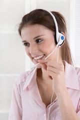 Lachende junge Frau in rosarot mit Headset in der Arbeit