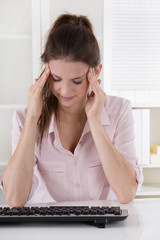 Frau sitzt mit Kopfschmerzen im Büro