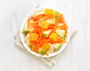 Fruit salad on white wooden table, top view