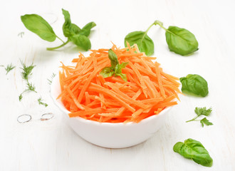 Grated carrot and herbs on white wooden table