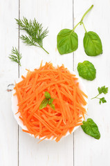 Grated carrot in bowl, top view