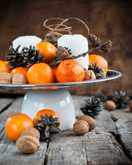 Holiday Composition with Tangerines, Pine cones, Walnuts on Wood
