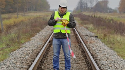 Railway engineer with tablet PC and warning tape