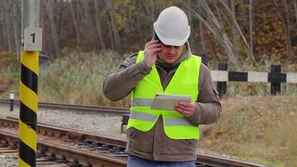 Railway engineer talking on cell phone near railway